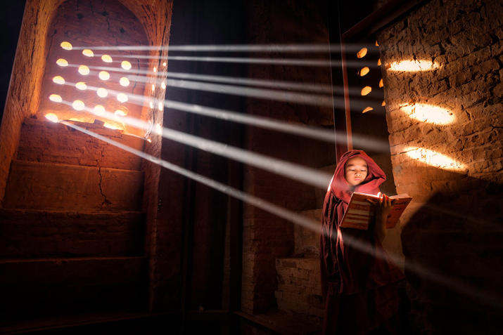 LightSource Young Monk finds a perfect light source to read his book inside of his pagoda - Old Bagan, Burma Location: Old Bagan