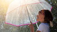 Wetter: Eine Frau hält einen Regenschirm.