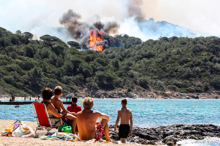 People enjoy the beach as they look at a forest fire in La Croix-Valmer, near Saint-Tropez, on July 25, 2017. Firefighters battle blazes that have consumed swathes of land in southeastern France for a second day, with one inferno out of control near the chic resort of Saint-Tropez, emergency services say.