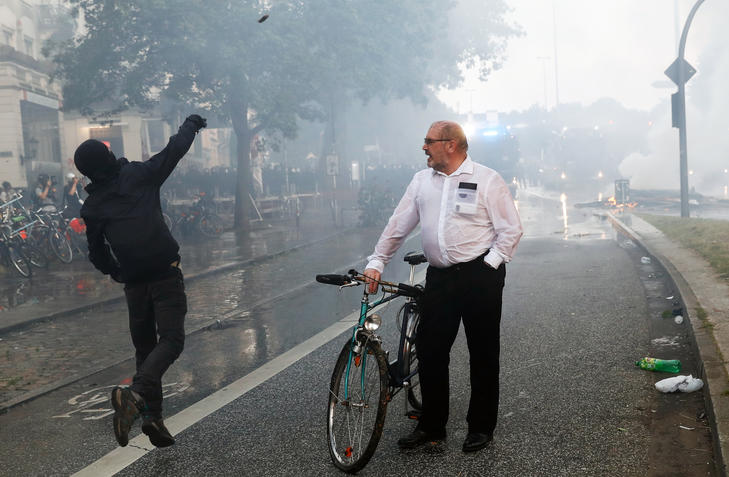 A man on his bike looks at a masked protester throwning a stone at riot police using water cannon on July 7, 2017 in Hamburg, northern Germany, where leaders of the world's top economies gather for a G20 summit. Protesters clashed with police and torched patrol cars in fresh violence ahead of the G20 summit, police said. German police and protestors had clashed already the day before at an anti-G20 march, with police using water cannon and tear gas to clear a hardcore of masked anti-capitalist demonstrators, AFP reporters said